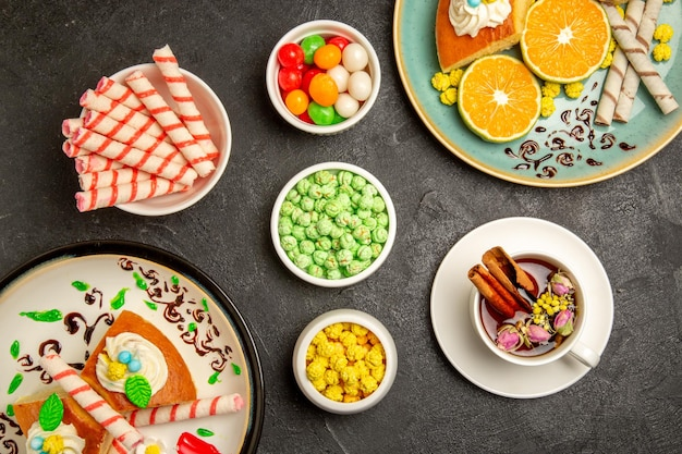 Widok z góry pyszne plastry ciasta z pokrojonymi mandarynkami na ciemnoszarym tle ciasto owocowe ciasto ciasto herbata herbata