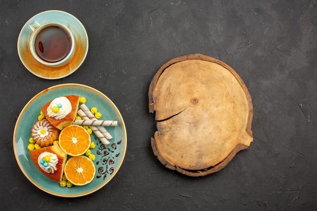 Widok z góry pyszne plastry ciasta ze świeżymi mandarynkami i filiżanką herbaty w ciemności
