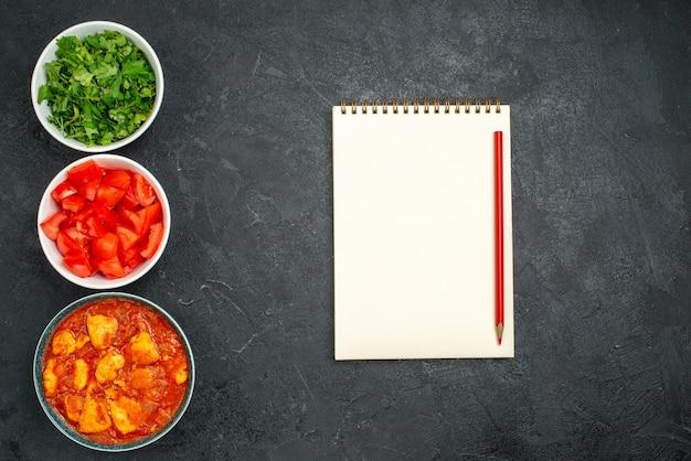Widok z góry pyszne plastry kurczaka z sosem pomidorowym i zieleniną na ciemnoszarym tle sos danie mięso kurczak pomidor