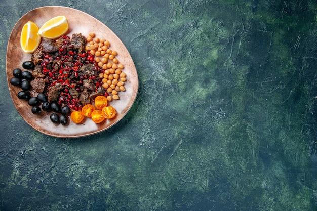Widok z góry pyszne plastry mięsa smażone z fasolą winogrona i plasterkami cytryny wewnątrz talerza, danie posiłek jedzenie mięso owocowe