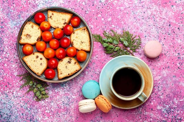 Widok z góry pyszne pokrojone ciasto z kwaśnymi, świeżymi śliwkami, makaronikami i herbatą na różowej powierzchni