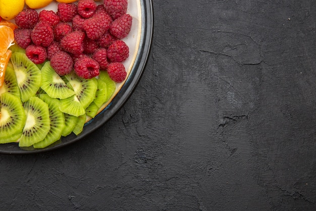 Widok z góry pyszne pokrojone owoce wewnątrz talerza na ciemnym tropikalnym drzewie owocowym egzotyczna dojrzała dieta zdjęcie wolne miejsce