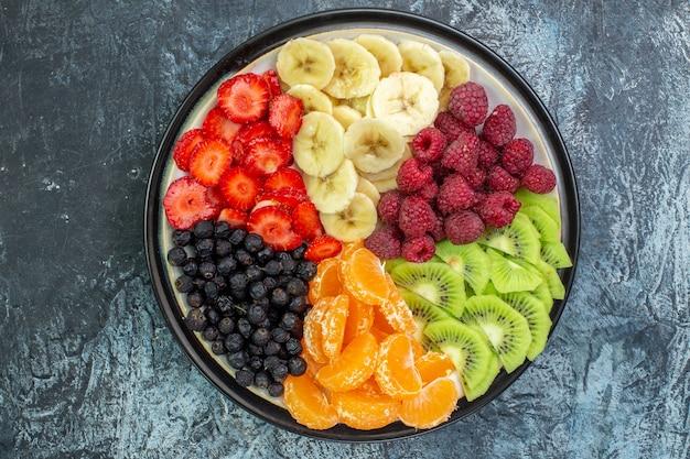 Widok z góry pyszne pokrojone owoce wewnątrz talerza na szarym egzotycznym kolorze zdrowe życie zdjęcie dojrzałe drzewo