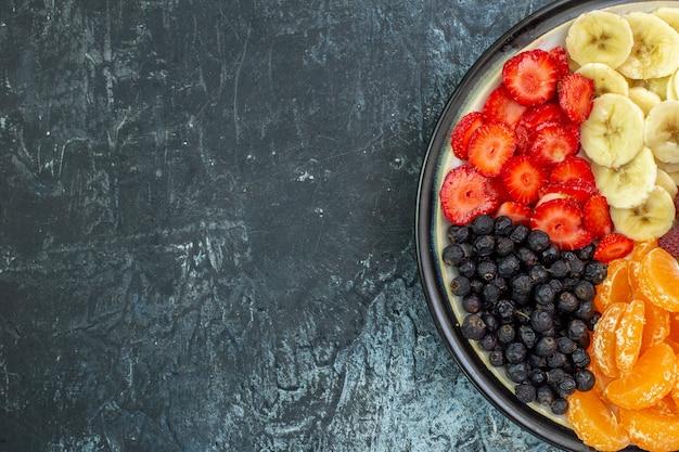 Widok z góry pyszne pokrojone owoce wewnątrz talerza na szarym egzotycznym kolorze zdrowe życie zdjęcie łagodne drzewo dojrzałe wolne miejsce