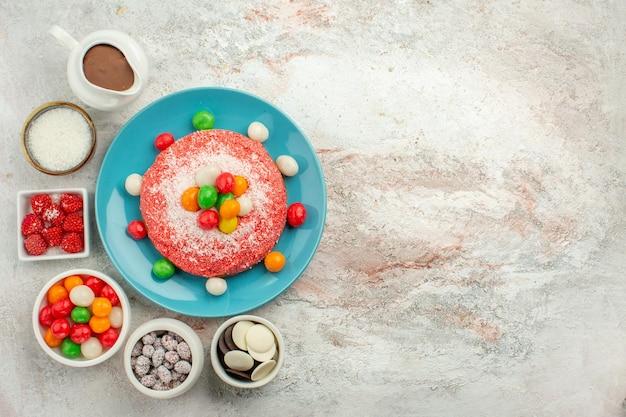 Widok z góry pyszne różowe ciasto z kolorowymi cukierkami i ciasteczkami na białej powierzchni