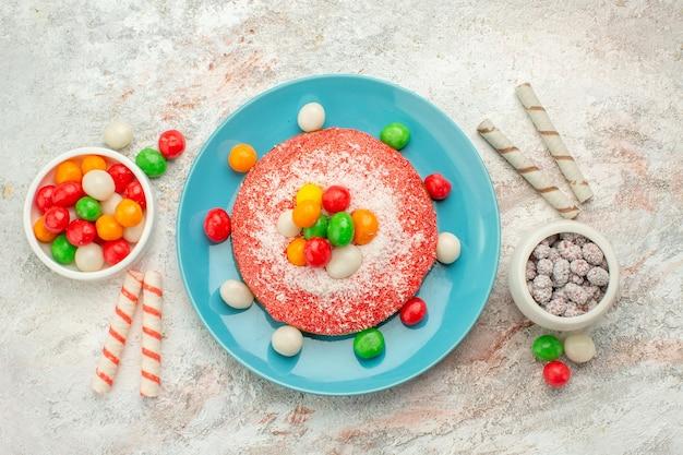 Widok z góry pyszne różowe ciasto z kolorowymi cukierkami na białej powierzchni cukierki deserowe w kolorze tęczy gadżety