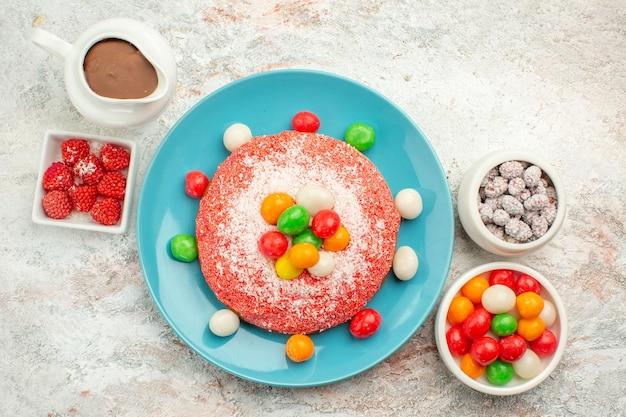 Widok z góry pyszne różowe ciasto z kolorowymi cukierkami na białej powierzchni kolor deserowy tort tęczowy cukierek