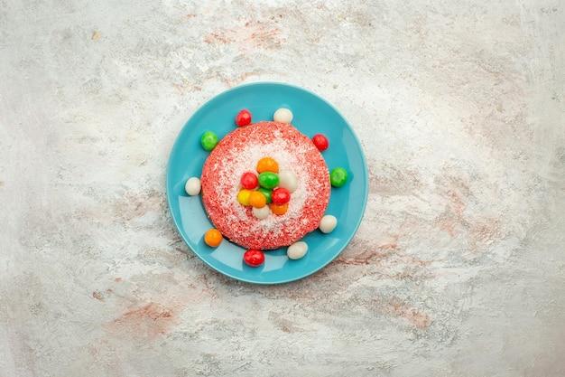 Widok z góry pyszne różowe ciasto z kolorowymi cukierkami wewnątrz talerza na białej powierzchni deser w kolorze tęczy cukierków