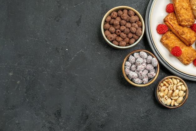 Widok z góry pyszne słodkie ciasteczka wewnątrz płyty na szarym tle herbatniki ciasteczka słodkie ciastka cukrowe herbata