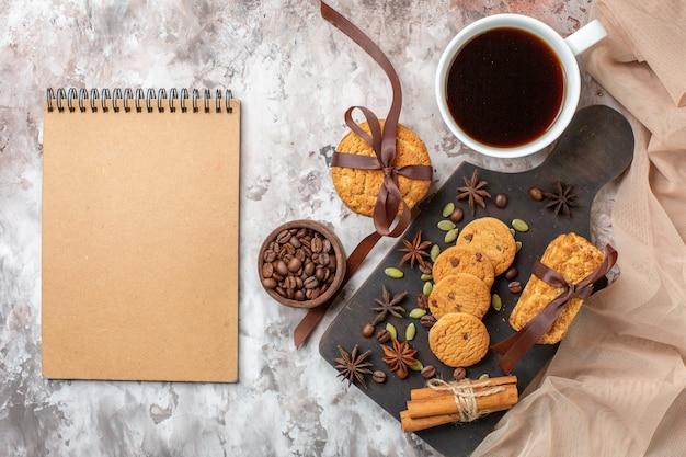 Widok z góry pyszne słodkie ciasteczka z ziarnami kawy i filiżanką kawy na jasnym tle cukier herbaciany słodki kolor ciasta kakaowego