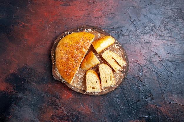 Widok z góry pyszne słodkie ciasto pokrojone w kawałki na ciemnej powierzchni
