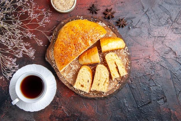 Widok z góry pyszne słodkie ciasto pokrojone w kawałki z herbatą na ciemnej powierzchni