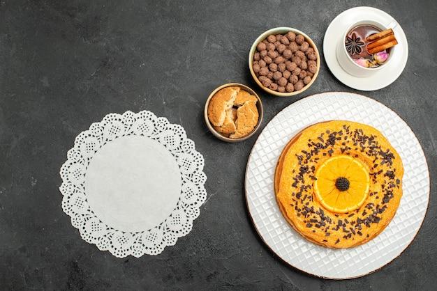 Widok z góry pyszne słodkie ciasto z filiżanką herbaty na ciemnej powierzchni ciasteczka ciasto herbatniki deserowe ciasto herbaciane