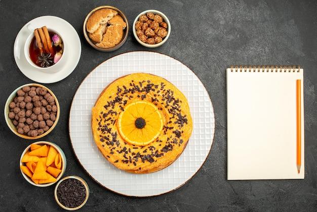 Widok z góry pyszne słodkie ciasto z plastrami pomarańczy i filiżanką herbaty na ciemnoszarej powierzchni