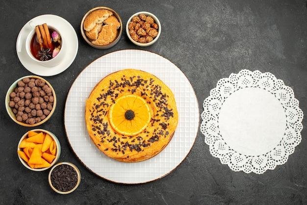 Widok z góry pyszne słodkie ciasto z plastrami pomarańczy i filiżanką herbaty na ciemnym biurku