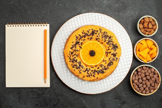 Widok z góry pyszne słodkie ciasto z pomarańczowymi plastrami na ciemnoszarej powierzchni ciasto deserowe ciastko z herbatą