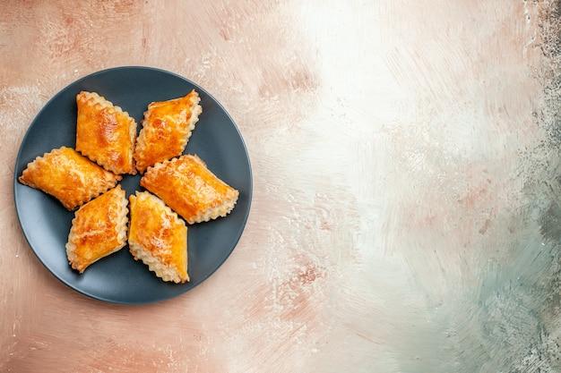 Widok z góry pyszne słodkie wypieki wewnątrz talerza na białym stole ciasto słodkie ciasto