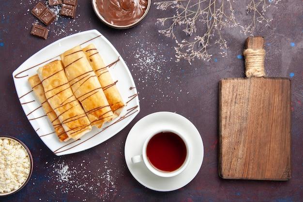 Widok z góry pyszne słodkie wypieki z czekoladą i filiżanką herbaty na ciemnym miejscu