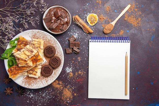 Widok z góry pyszne słodkie wypieki z czekoladowymi ciasteczkami w ciemnej przestrzeni