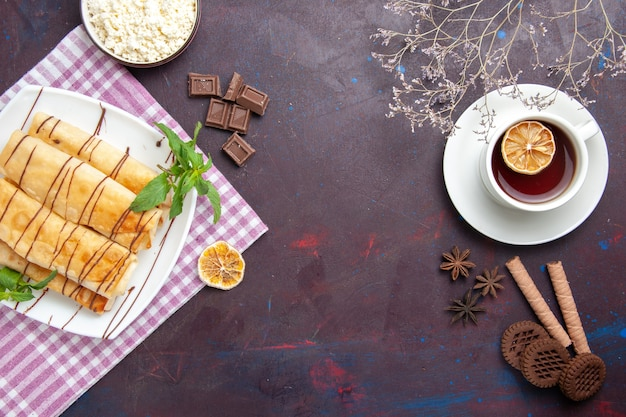 Widok z góry pyszne słodkie wypieki z filiżanką herbaty w ciemnej przestrzeni