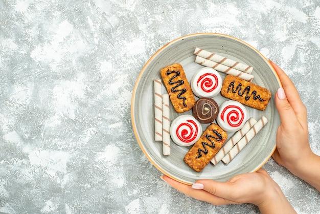 Widok z góry pyszne słodycze, ciasta i ciasteczka na białej przestrzeni