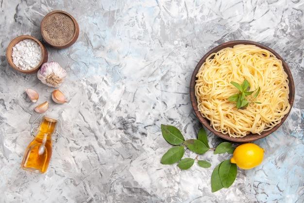 Widok z góry pyszne spaghetti wewnątrz talerza na białym stole posiłek danie z ciasta makaron