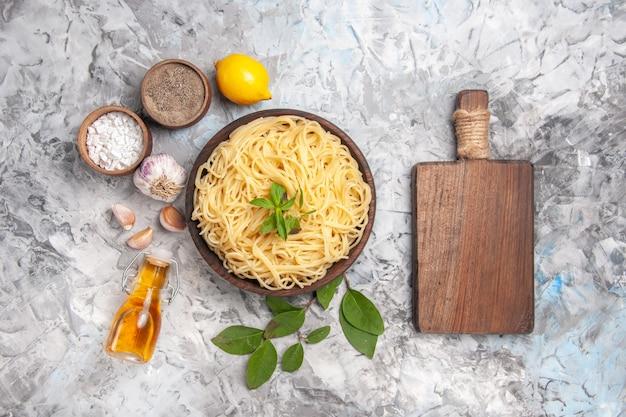 Widok z góry pyszne spaghetti wewnątrz talerza na białym stole z mąką z ciasta
