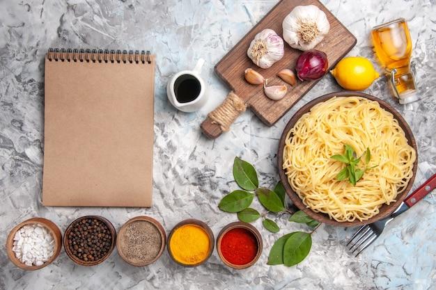 Widok z góry pyszne spaghetti z przyprawami na białym stole w kolorze ciasta makaronowego