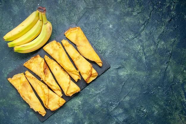 Widok z góry pyszne walcowane naleśniki z bananami na ciemnym tle ciasto ciasto hotcake kolor posiłek ciasto słodkie ciasto mięso wolna przestrzeń