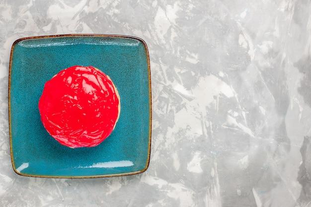 Widok z góry pyszne wyglądające ciasto małe ciasto z czerwonym kremem na białym tle ciasto herbatniki piec cukier śmietankowy słodkie