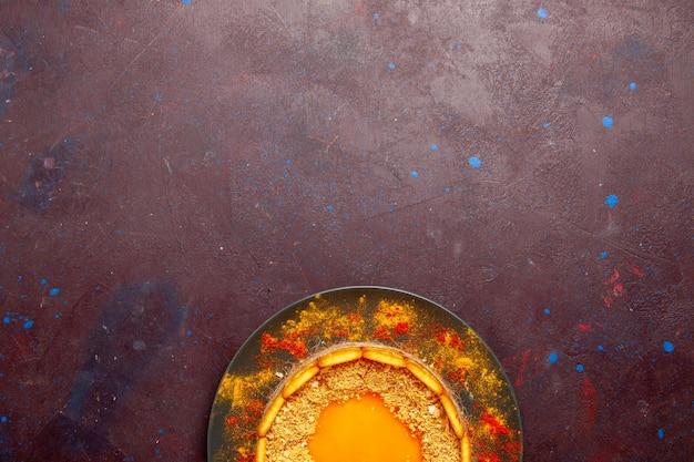 Widok z góry pyszne żółte ciasto z ciasteczkami biszkoptowymi i kremem na ciemnej powierzchni