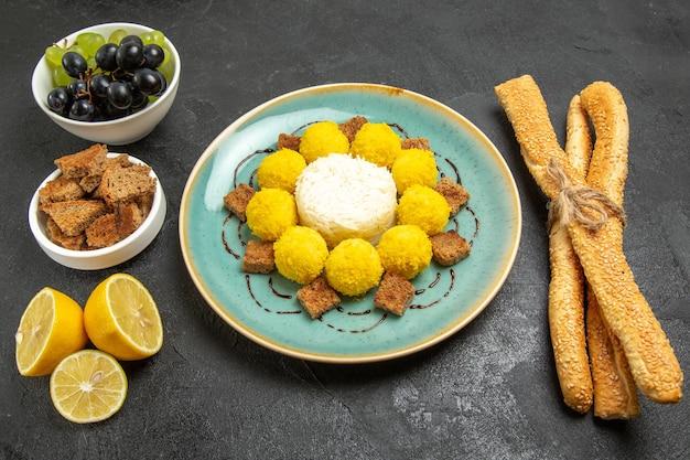 Widok z góry pyszne żółte cukierki z winogronami i chlebem na ciemnym tle cukier owocowy cukierek herbata ciasto słodkie