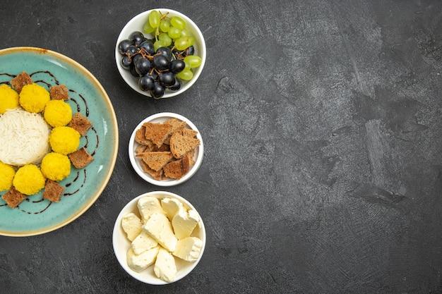 Widok z góry pyszne żółte cukierki z winogronami i serem na ciemnym tle cukier owocowy cukierek herbata ciasto słodkie