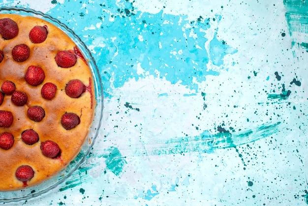 Widok z góry pysznego ciasta truskawkowego w kształcie okrągłym z owocami na wierzchu na jasnoniebieskim, ciastowym słodkim ciastku z cukrem i jagodami