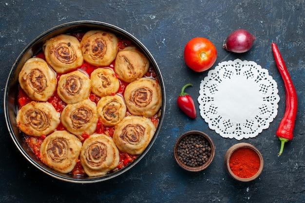 Widok z góry pysznego ciasta z mięsem na patelni wraz ze świeżymi warzywami, takimi jak cebula, pomidory na ciemnoszarym biurku, potrawa mięsna