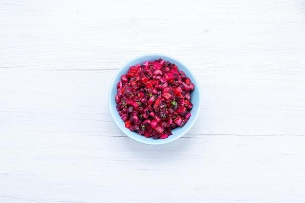 Widok z góry pysznej sałatki z buraków pokrojonej w plasterki z zieleniną wewnątrz niebieskiego talerza na jasnej podłodze warzywna witamina jedzenie posiłek zdrowe sałatki
