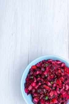 Widok z góry pysznej sałatki z buraków pokrojonej z zieleniną i warzywami wewnątrz niebieskiego talerza na lekkim biurku, witaminowy posiłek warzywny, zdrowa sałatka