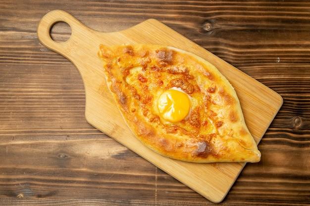 Widok z góry pyszny chleb jajeczny pieczony na brązowym drewnianym stole bułka chlebowa piec śniadanie jajko