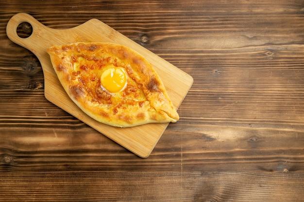 Widok z góry pyszny chleb jajeczny pieczony na brązowym drewnianym stole chleb bułka piec śniadanie ciasto jajeczne