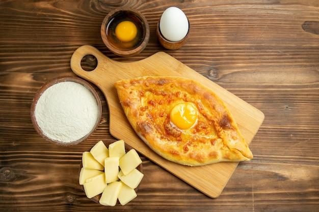 Widok z góry pyszny chleb jajeczny pieczony na brązowym drewnianym stole chleb bułka piec śniadanie jajka ciasto