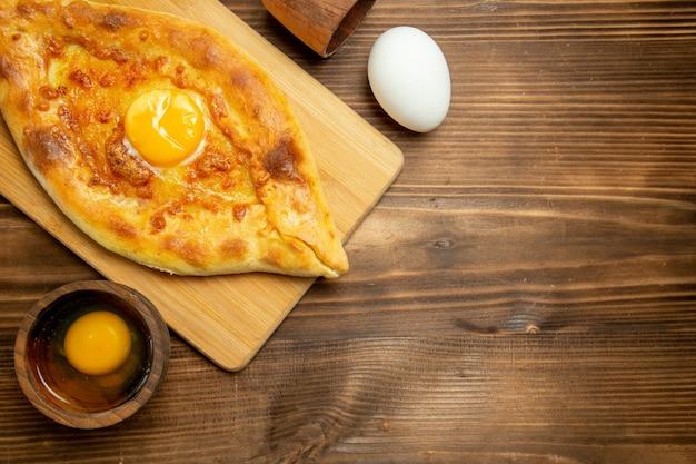 Widok z góry pyszny chleb jajeczny pieczony na brązowym drewnianym stole chleb piec śniadanie jajko