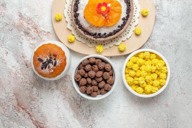 Widok z góry pyszny deser czekoladowy z mandarynkami i cukierkami na białym tle kremowe ciasto biszkoptowe deser owocowy