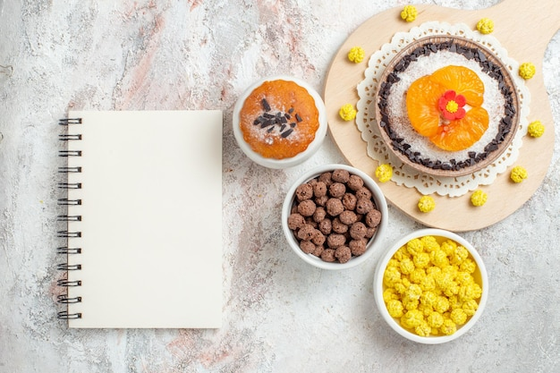 Widok z góry pyszny deser czekoladowy z mandarynkami i cukierkami na białym tle kremowy deser ciasto biszkoptowe owocowe