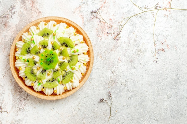 Widok z góry pyszny deser kiwi z pyszną białą śmietaną i pokrojonymi owocami na białym tle deser ciasto kremowe owoce tropikalne