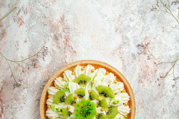 Widok z góry pyszny deser kiwi z pyszną białą śmietaną i pokrojonymi owocami na jasnym białym tle deser ciasto kremowe owoce tropikalne