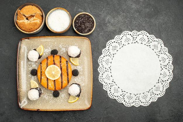 Widok z góry pyszny deser na ciasto z cukierkami kokosowymi na ciemnej powierzchni ciasto deserowe słodkie cukierki herbata