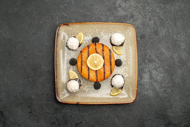 Widok z góry pyszny deser na ciasto z plasterkami cytryny i cukierkami kokosowymi na ciemnej powierzchni herbata deserowa słodkie ciasto z ciasta cukierkowego