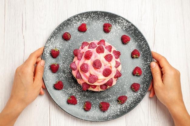 Widok z góry pyszny deser z ciasta owocowego ze świeżymi malinami na białym tle słodki deser z herbatą kremową ciasto z ciastkami
