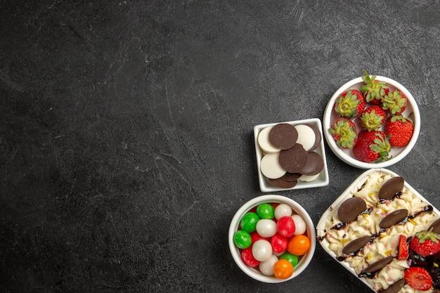 Widok z góry pyszny deser z ciasteczkami i cukierkami na ciemnym tle orzechowe herbatniki słodkie owocowe ciasteczka cukier