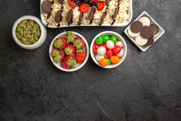 Widok z góry pyszny deser z ciasteczkami i cukierkami na ciemnym tle orzechy herbatniki słodkie ciasteczka owocowe cukier